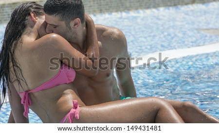 Young couple kissing each other while laying in swimming pool on a hot summer day  - stock photo