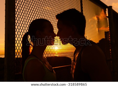 Young couple kissing in a beautiful outdoor setting - stock photo