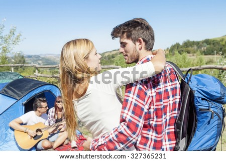 young couple kissing in a camping of the hill