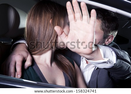 Young couple kissing in car and man is shielding with his arm  - stock photo