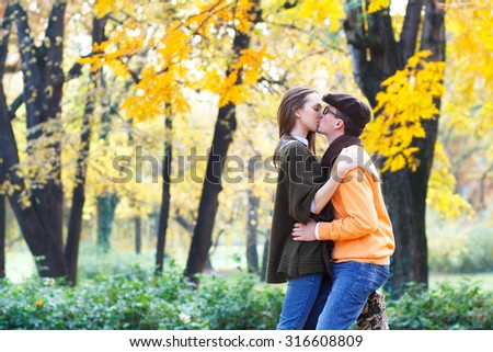 Young couple kissing in park. - stock photo