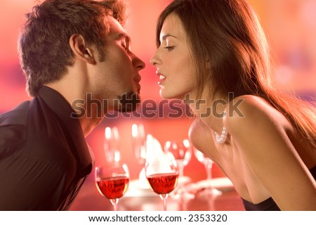 Young couple kissing in restaurant, celebrating or on romantic date - stock photo