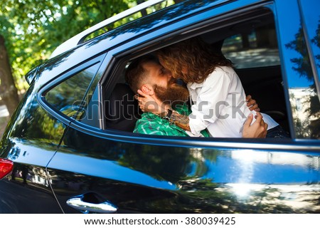 Young couple kissing in the back seat of the car. - stock photo