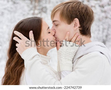 Young couple kissing in winter forest - stock photo