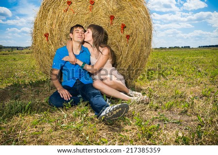 Young couple kissing near hay stack - stock photo
