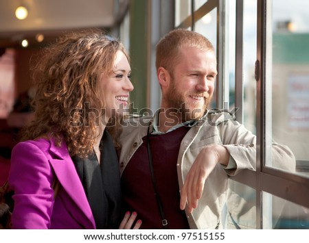 Young couple kissing near the window inside the building. - stock photo