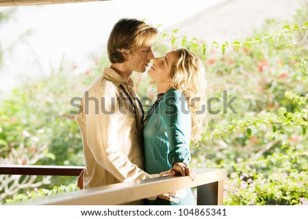 Young couple kissing on a tropical home's balcony overlooking a lush garden while on honeymoon. - stock photo
