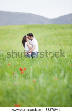 Young couple kissing on green field - stock photo