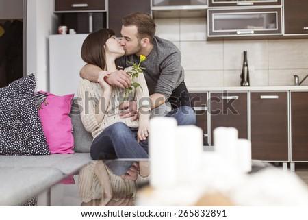 Young couple kissing on sofa - stock photo
