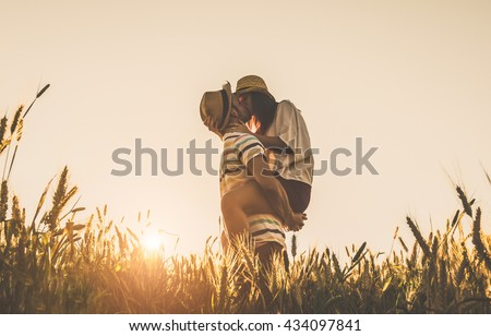 Young couple kissing on the background of a sunset in the wheat field - stock photo