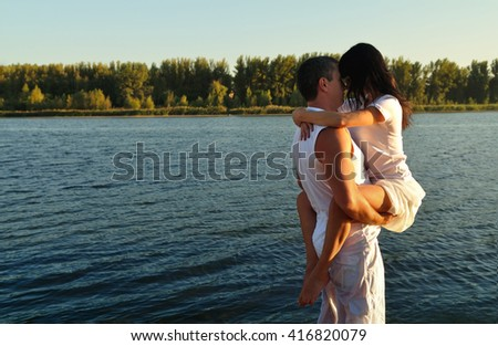 Young couple kissing on the background of the river - stock photo