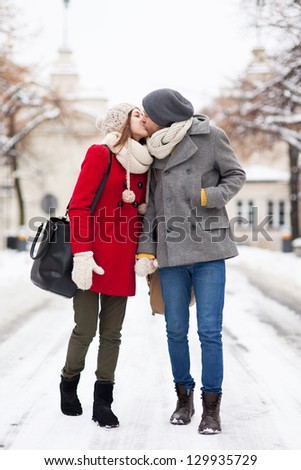 Young couple kissing on winter day - stock photo