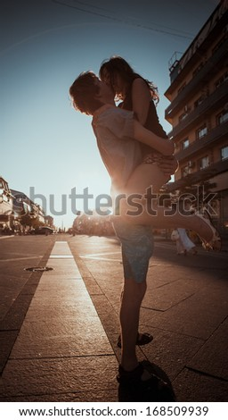 Young couple kissing over sunset - stock photo