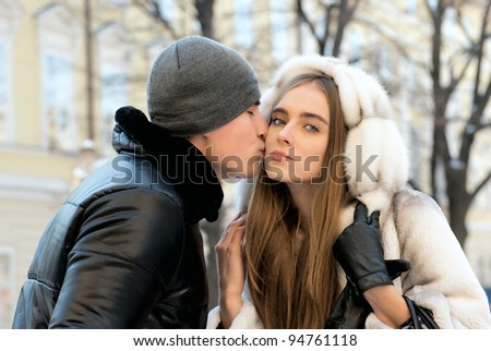 Young couple kissing winter outdoors portrait
