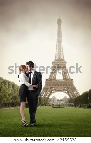 Young couple kissing with Eiffel Tower on the background - stock photo