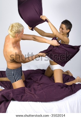 Young couple kneeling and fighting in bed with pillows. Gray background - stock photo