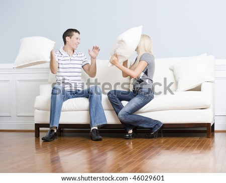 Young couple laugh while having a pillow fight on the sofa. Horizontal shot.
