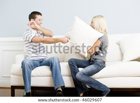 Young couple laugh while having a pillow fight on the sofa. Horizontal shot. - stock photo