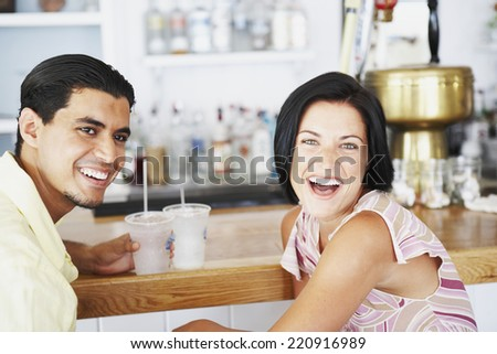 Young couple laughing at bar - stock photo