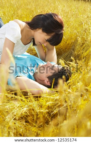 young couple laying down in meadow and hugging - stock photo