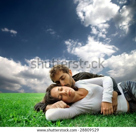 young couple laying in a grass field - stock photo