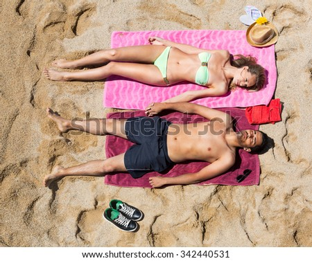 Young couple laying on the sandy beach at the sea shore in a sunny day  - stock photo
