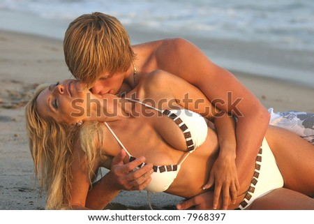 Young couple laying on their sides at the beach embracing with the Man from behind - stock photo