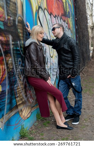 Young couple leaning against wall with graffiti looking unhappy - stock photo