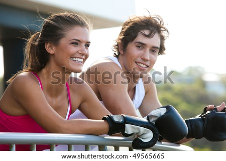 Young couple leaning over a railing in an outdoor setting. They are both wearing boxing gloves and smiling. Horizontal shot. - stock photo