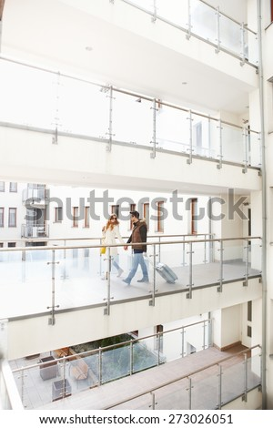 Young couple leaving apartment house at the end of city break. - stock photo