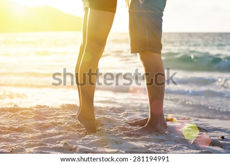 Young couple legs on the beach sand. Travel summer tropic holidays. Sunset silhouette of kissing newlyweds lovers hugging in front of ocean. Honeymoon vacation romantic sea view on Seychelles islands