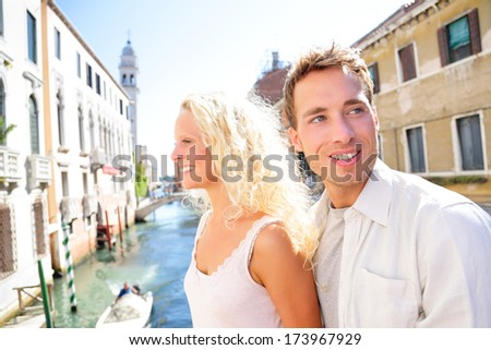 Young couple lifestyle walking in Venice on travel together. Happy couple on holidays or honeymoon having cute romantic vacation together in Venice on walk by Canal, Italy, Europe. - stock photo