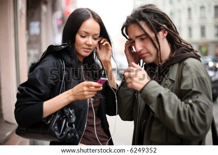 Young couple listening to a portable mp3 music player on a street in a city. Shallow DOF, focus on girl.