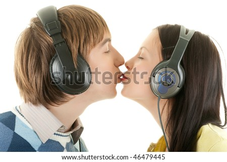 Young couple listening to music and kissing - stock photo