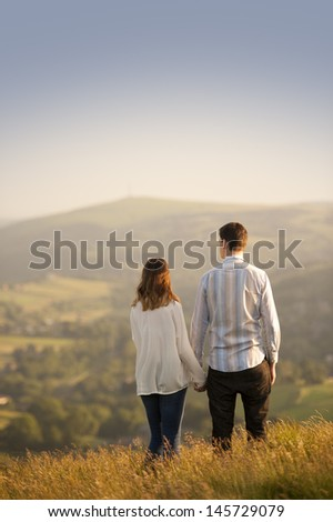 young couple look out over a beautiful landscape - stock photo