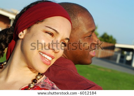 Young couple looking ahead toward the future while standing outside in the park - stock photo