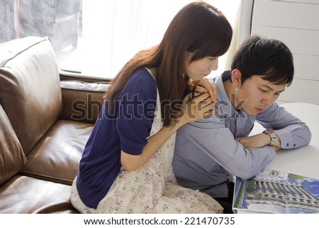 Young couple looking at advertisement of condominium