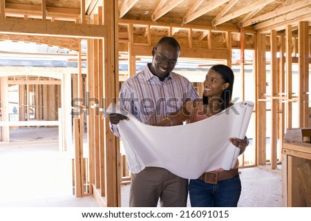Young couple looking at blueprints in partially built house, smiling - stock photo