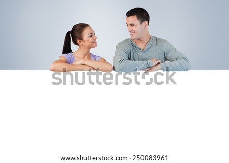 Young couple looking at each other while leaning on a wall against grey vignette