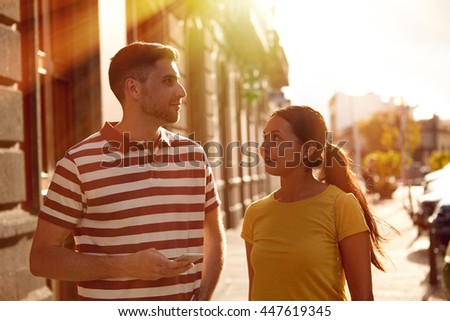 Young couple looking at each other while talking and smiling happily and dressed casually in t-shirts with old buildings behind them
