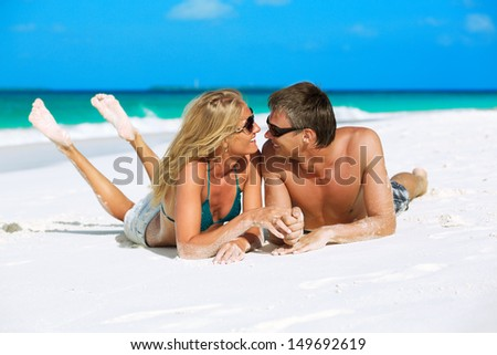 Young couple looking at each other with love, holding hands and enjoying their tropical vacation on Maldives