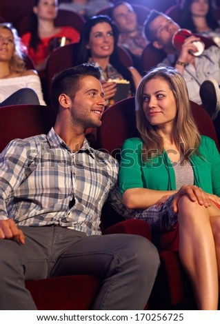 Young couple looking at each other with love, sitting in auditorium of cinema, smiling. - stock photo