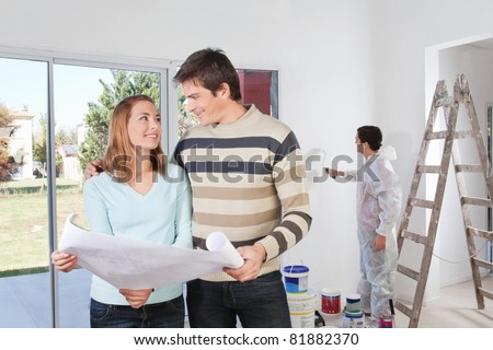 Young couple looking at each other with painter in background - stock photo