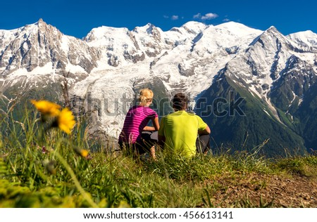 Young couple looking at panorama of Mont Blanc glacier from another hill, Chamonix, France, during famos trek - Tour du Mont Blanc - stock photo