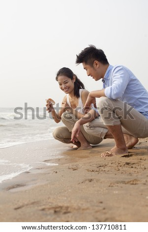 Young couple looking at seashell at the waters edge, China