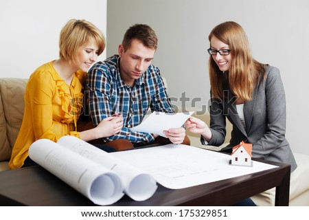 Young couple looking at some future house documents - stock photo