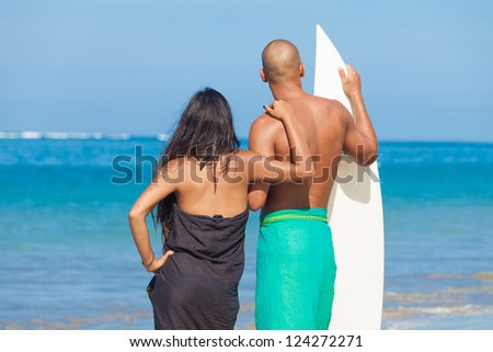 Young couple looking at surf with surfboard on beach - stock photo