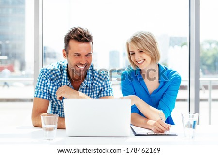 Young couple looking at the laptop display and smiling - stock photo