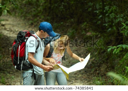 Young couple looking at the map in the forest - stock photo