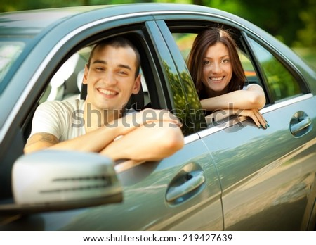 Young couple looking from their car leaving for vacation.